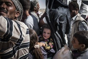 16/ Syrian Kurdish refugees who have crossed into Turkey wait in a holding area before boarding buses, after fleeing fighting between Kurdish forces and IS around the city of Kobani in North East Syria. UNHCR / I. Prickett / September 2014